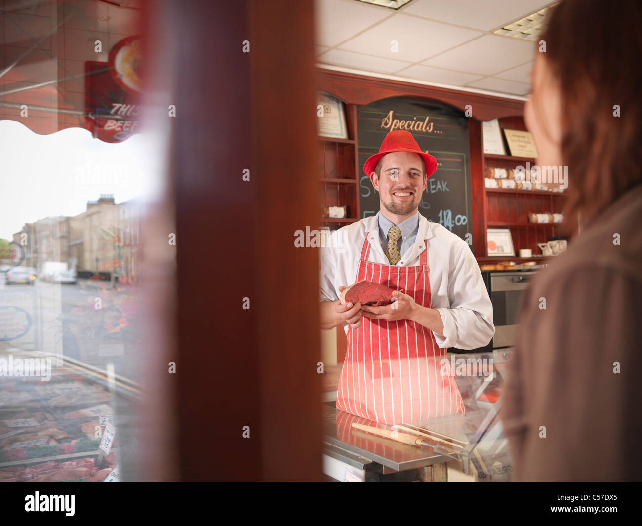 Butcher showing meat to customer - Stock Image