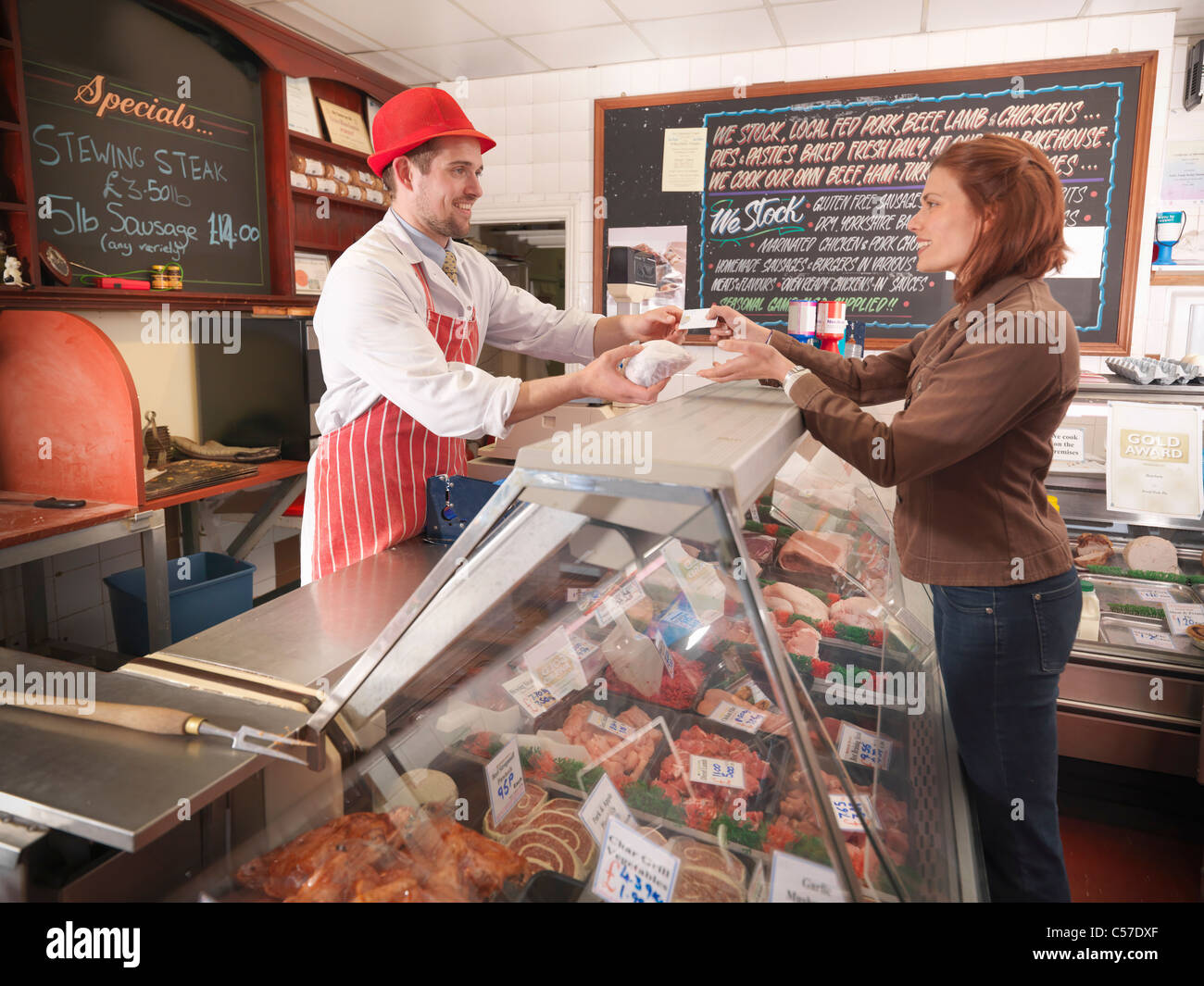 Butcher handing meat to customer - Stock Image