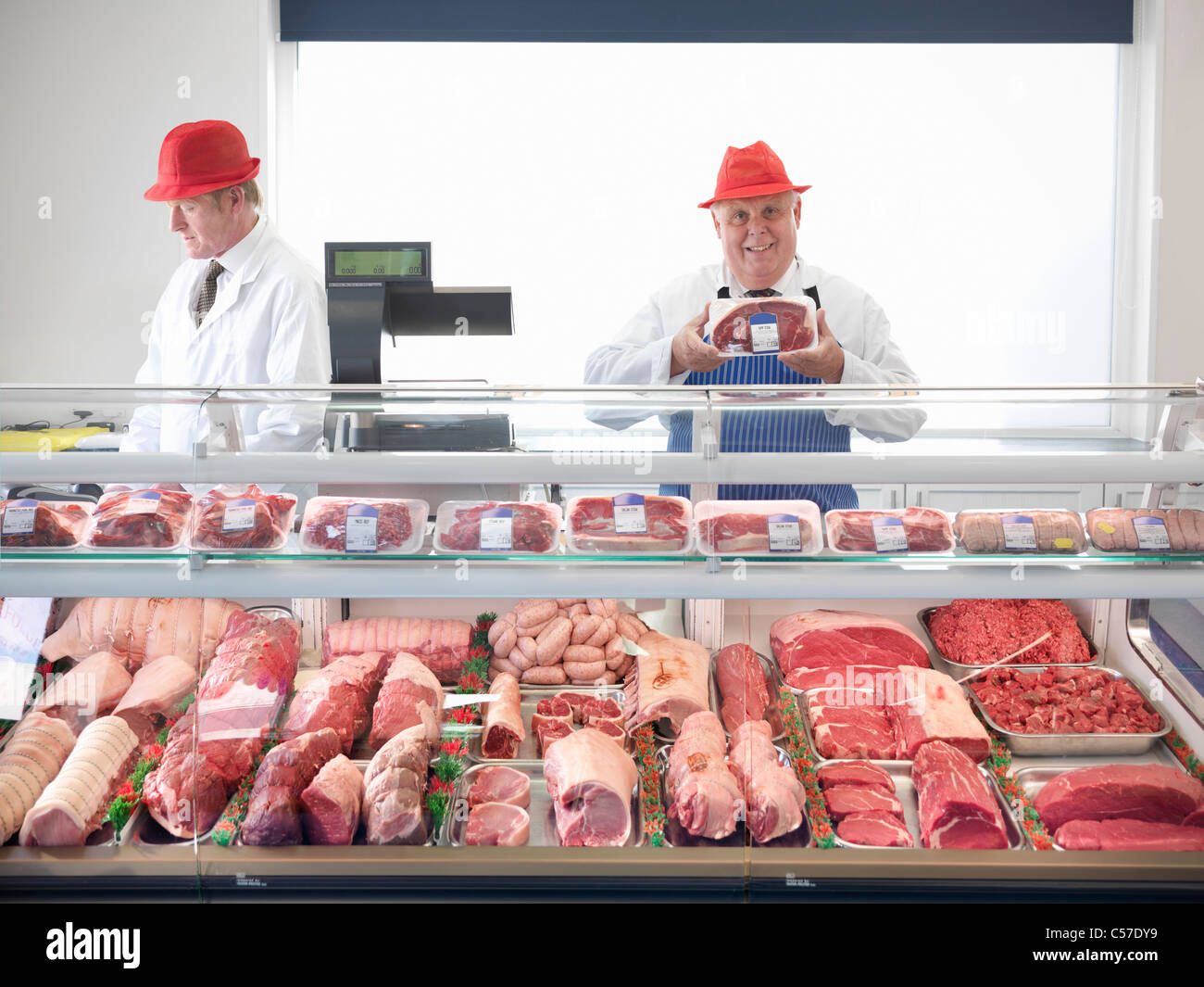 Butcher standing behind meat counter Stock Photo