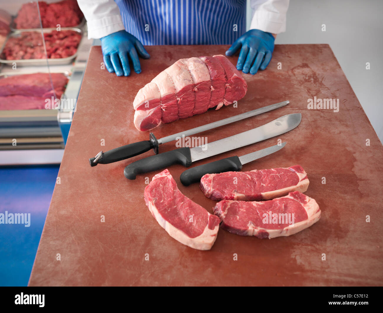 Butcher with knives and cuts of pork - Stock Image