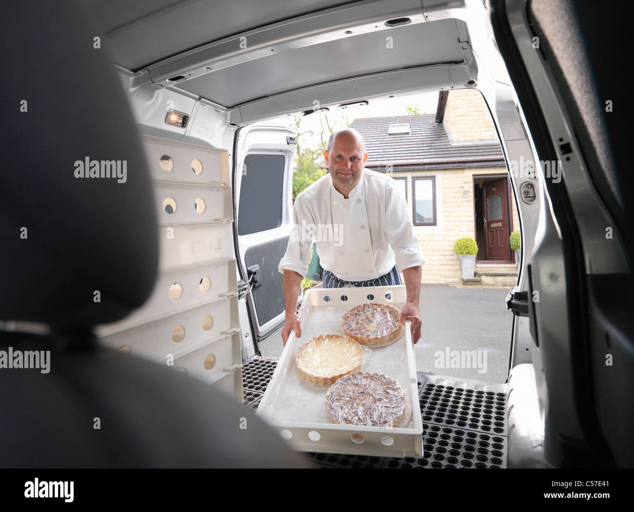 Pastry chef loading cakes into van - Stock Image