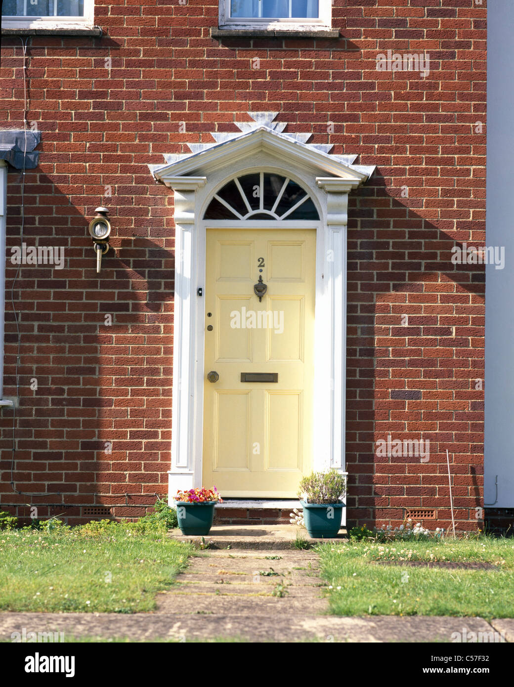 Doors   Modern Red Brick House With Mock Georgian Yellow Painted Wooden Door  Flanked By Columns And With Fanlight Above.