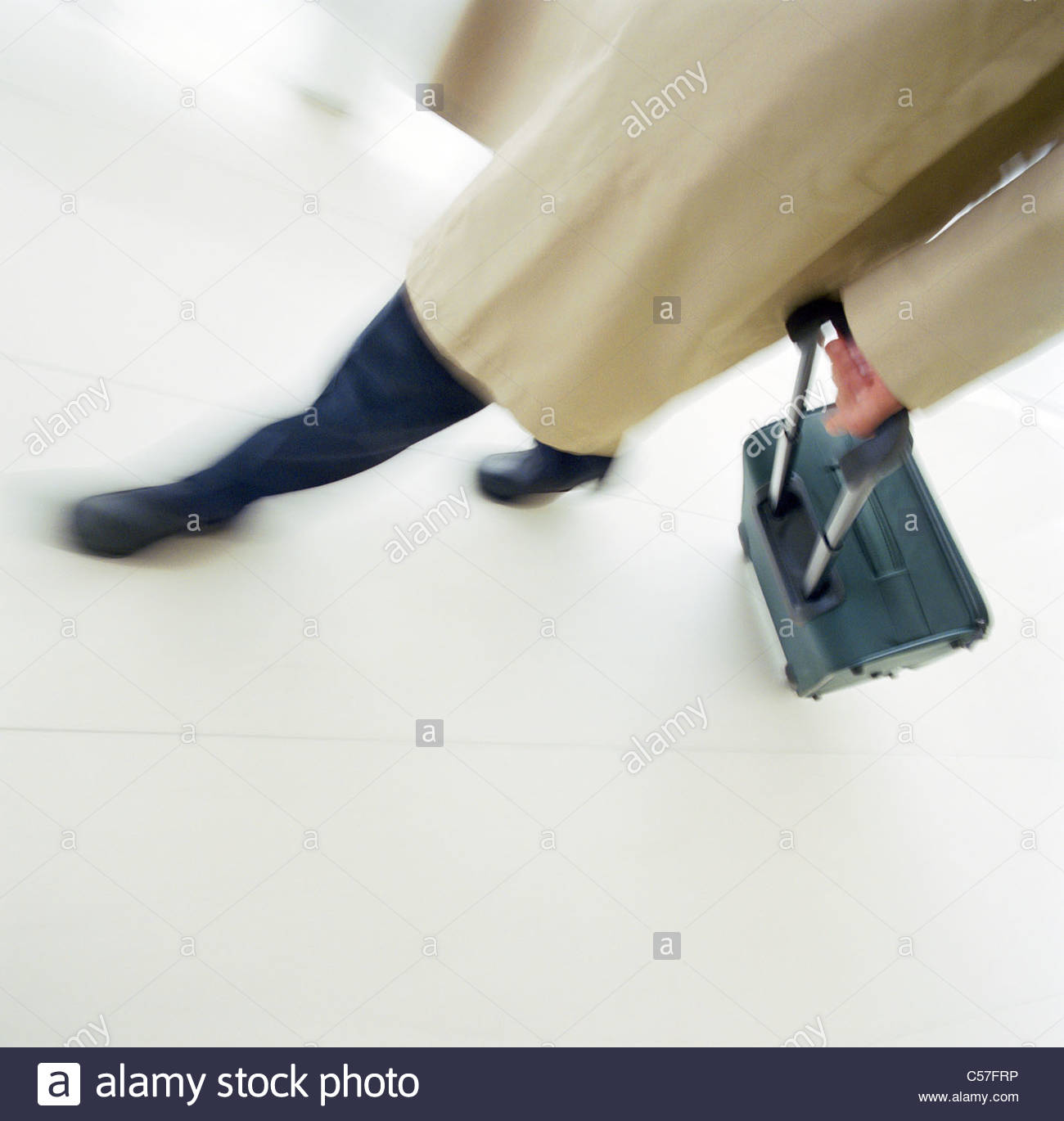 Business person rolling luggage - Stock Image