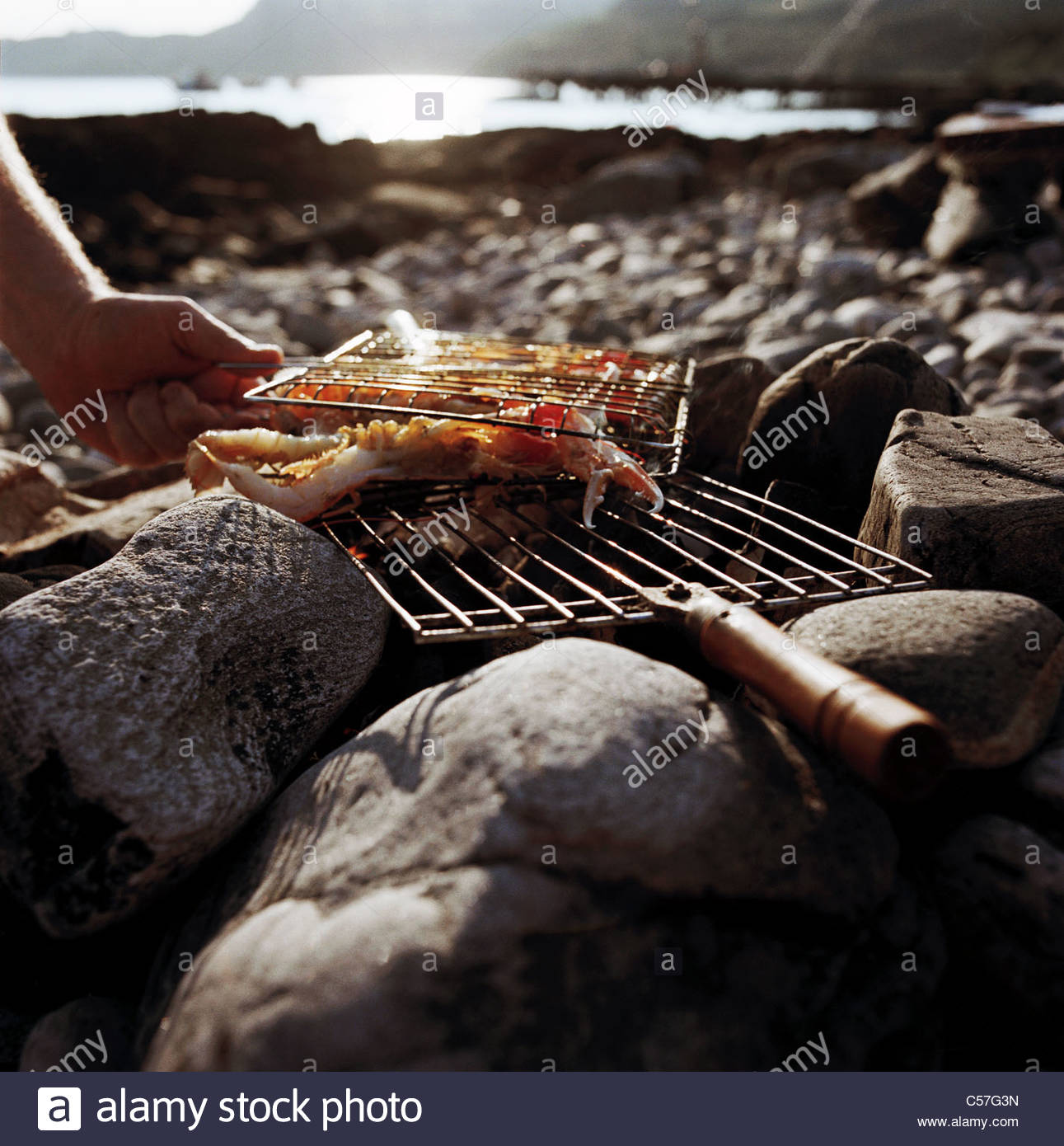 Man grilling seafood over fire on beach - Stock Image