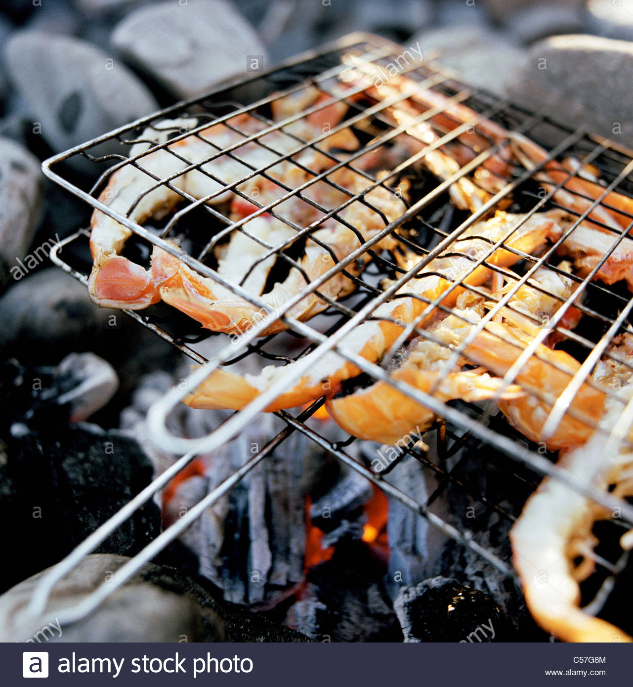 Close up of prawns grilling over fire - Stock Image