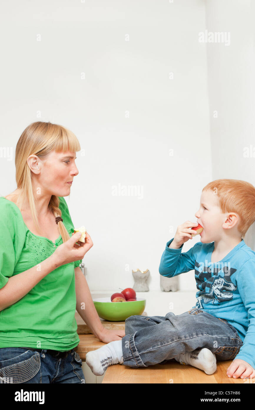 Mother and son eating apples together - Stock Image