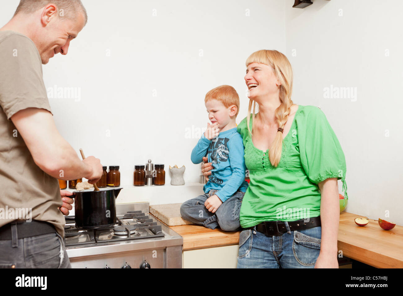 Parents cooking for reluctant son - Stock Image