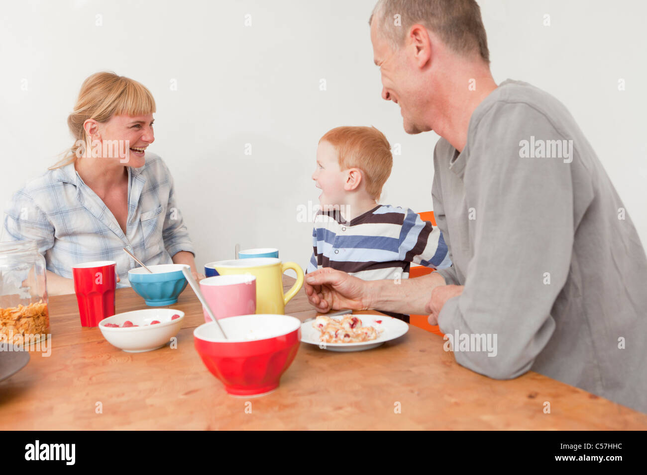 Family laughing at breakfast - Stock Image