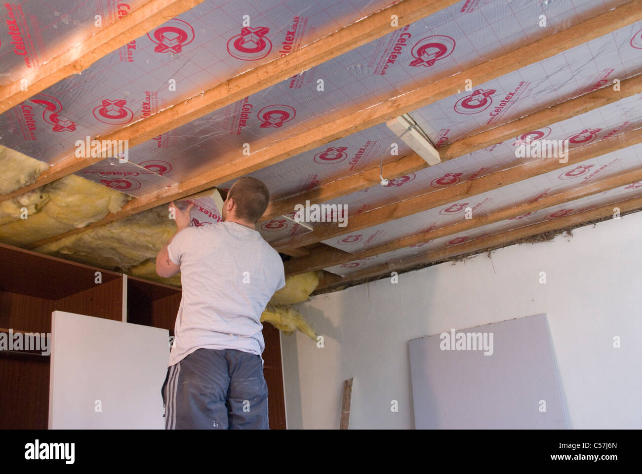 Builders installing high performance Kingspan Therma and Celotex insulation boards to the walls and ceiling of an - Stock Image