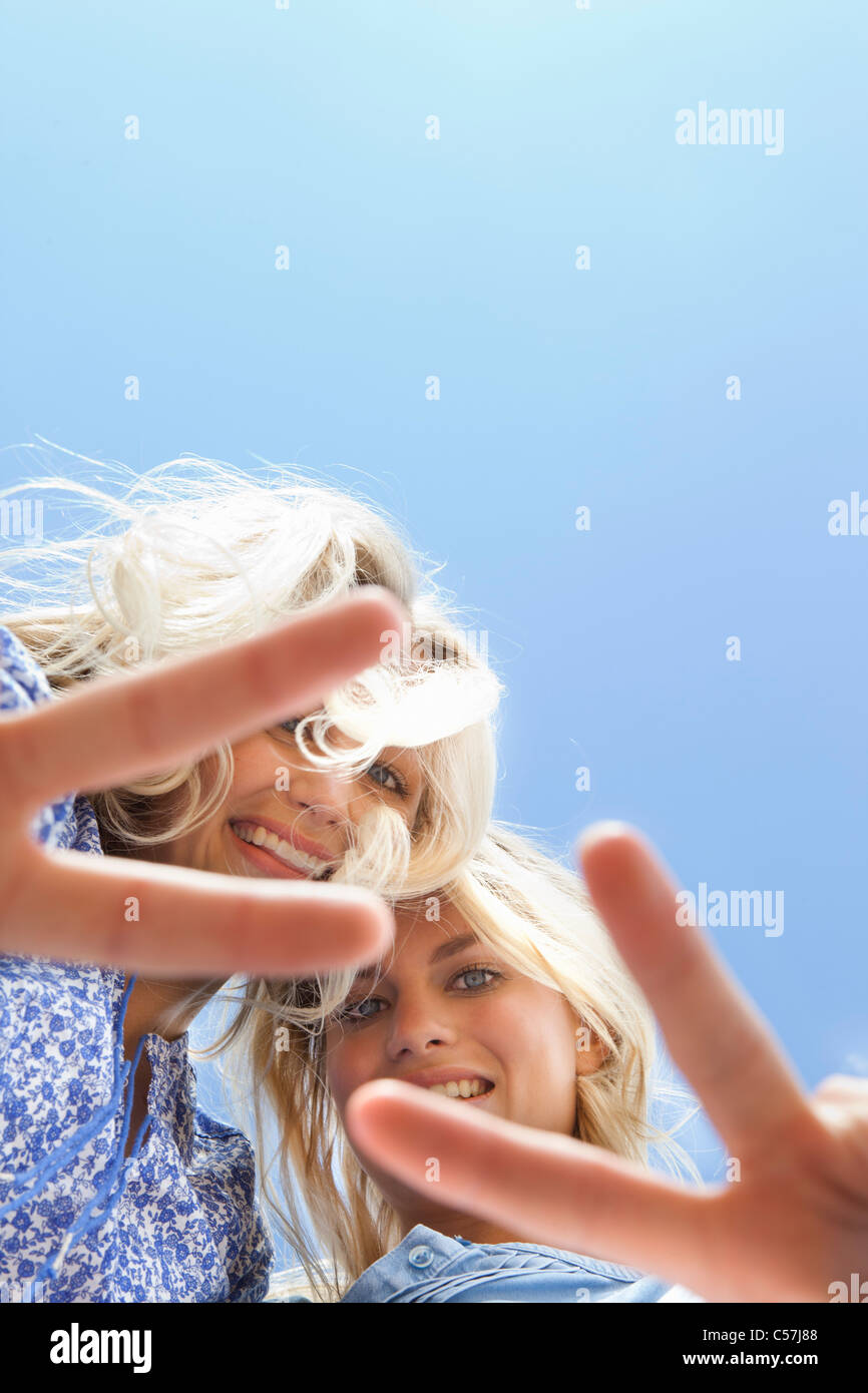 Sisters making peace sign together - Stock Image