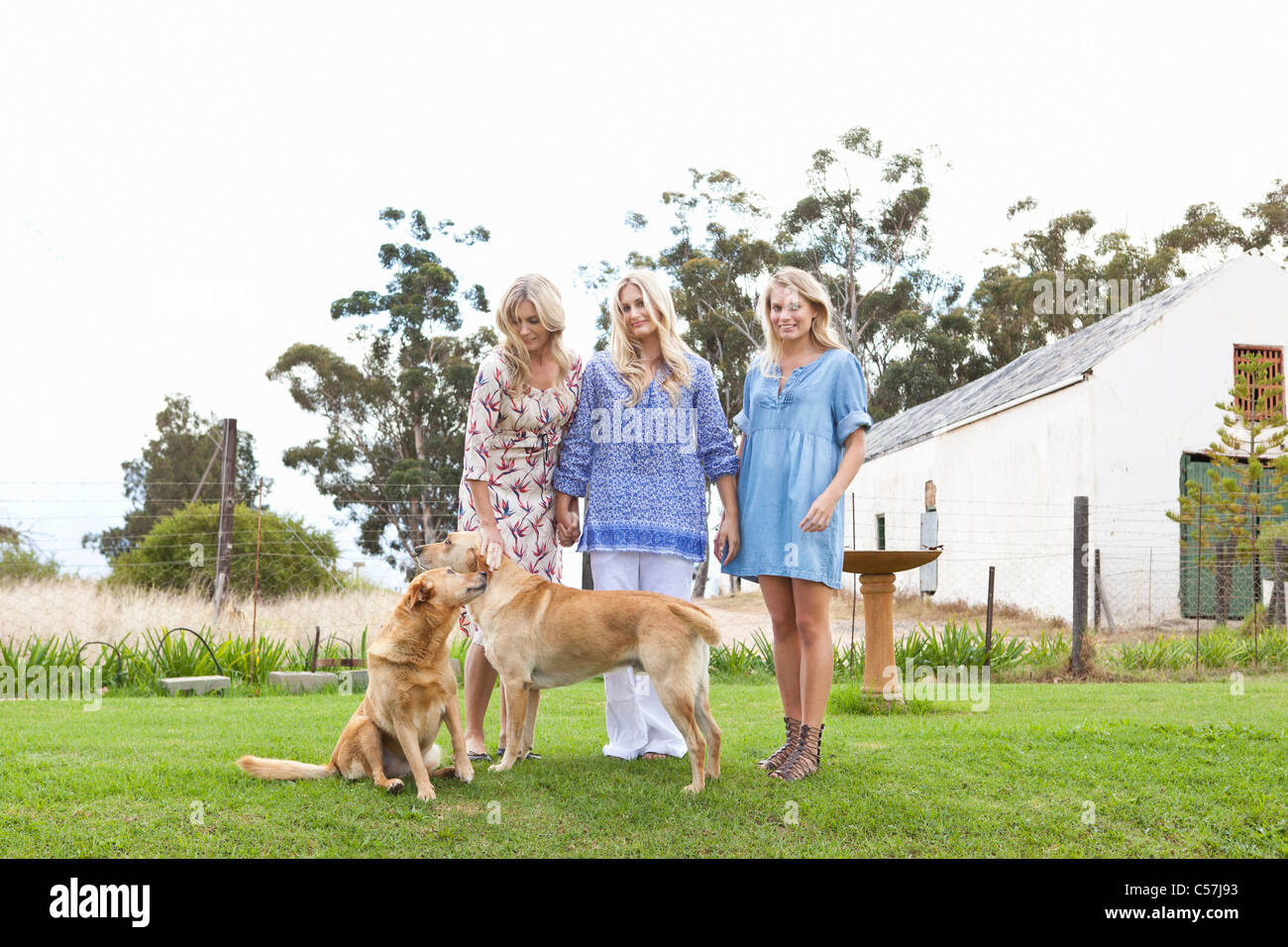 Mother and daughters with dogs in garden Stock Photo