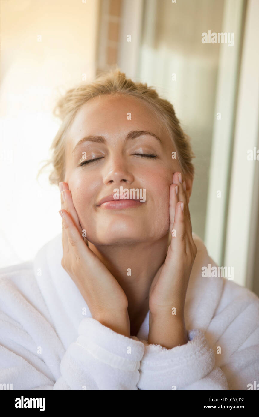 Woman rubbing moisturizer on face - Stock Image