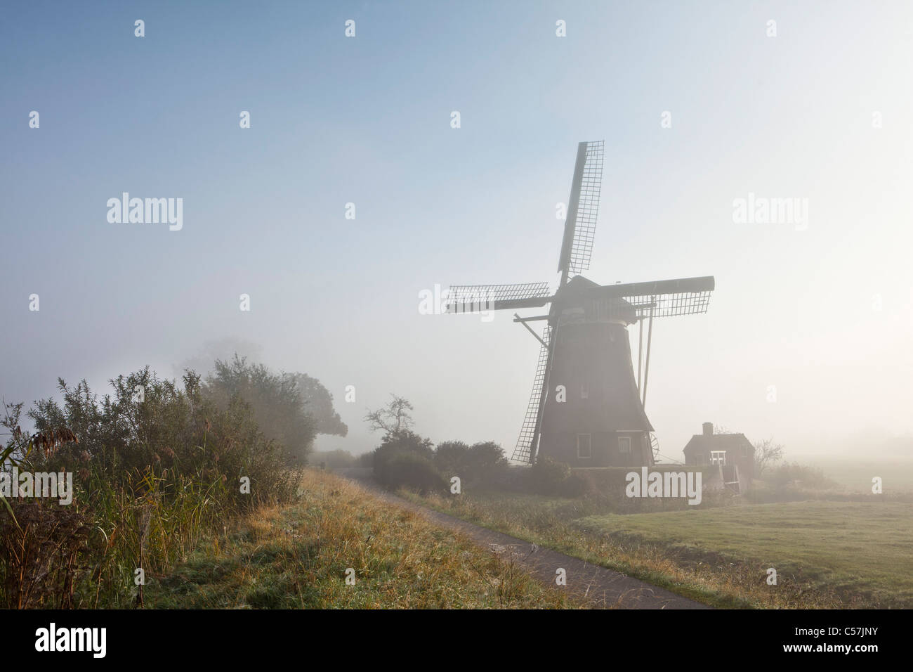 The Netherlands, Nigtevecht, Windmill in morning mist. - Stock Image