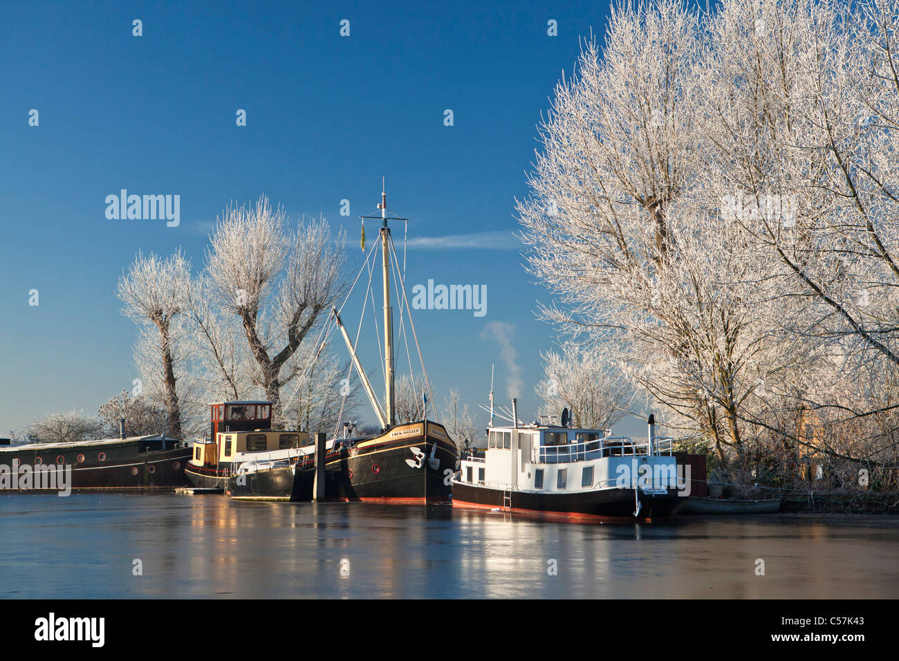The Netherlands, Nigtevecht, Boats in river called Vecht. Winter, frost. - Stock Image