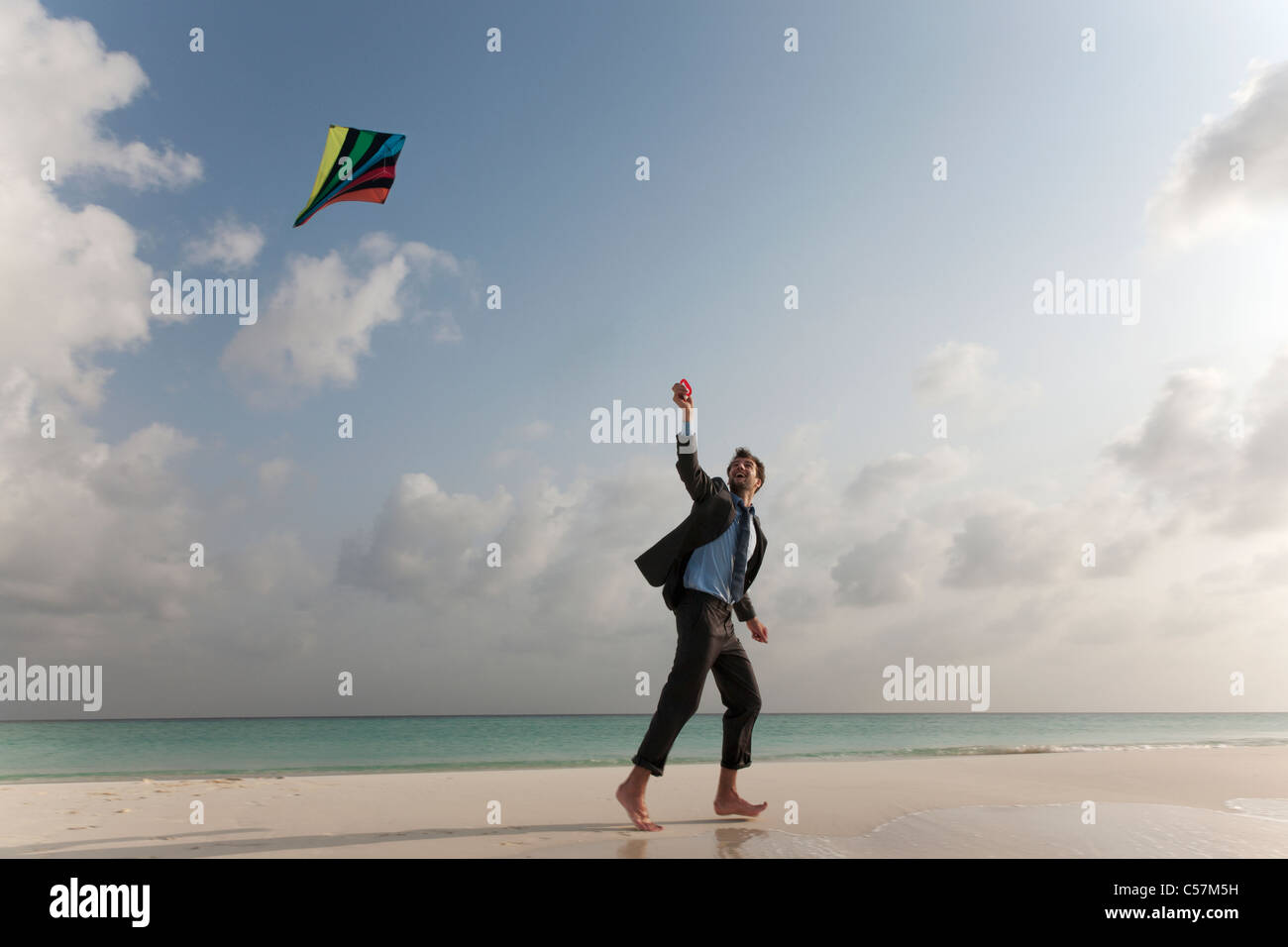 Businessman flying a kite on beach Stock Photo