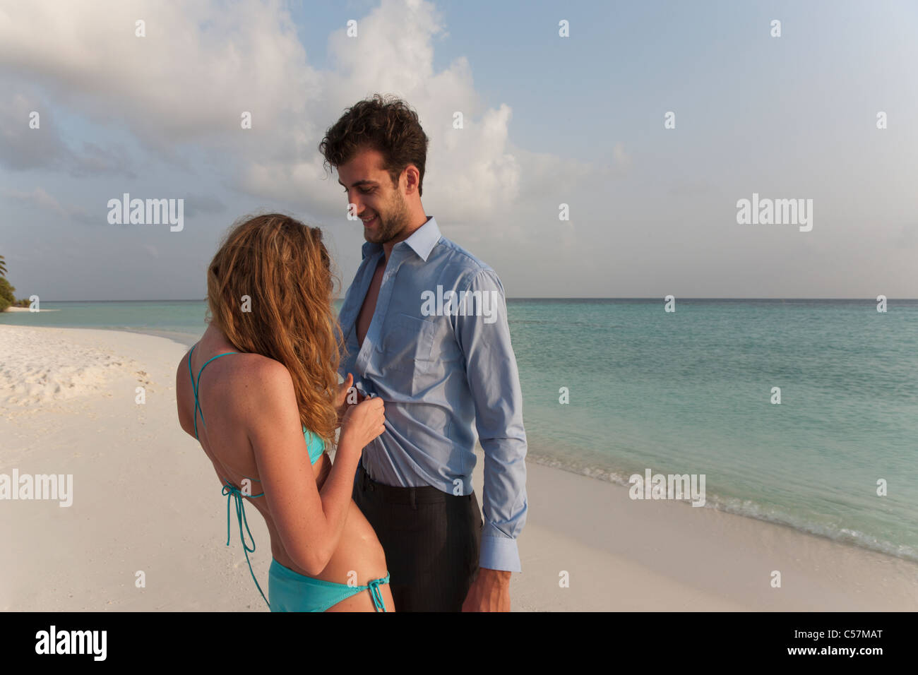 Woman undressing businessman on beach - Stock Image
