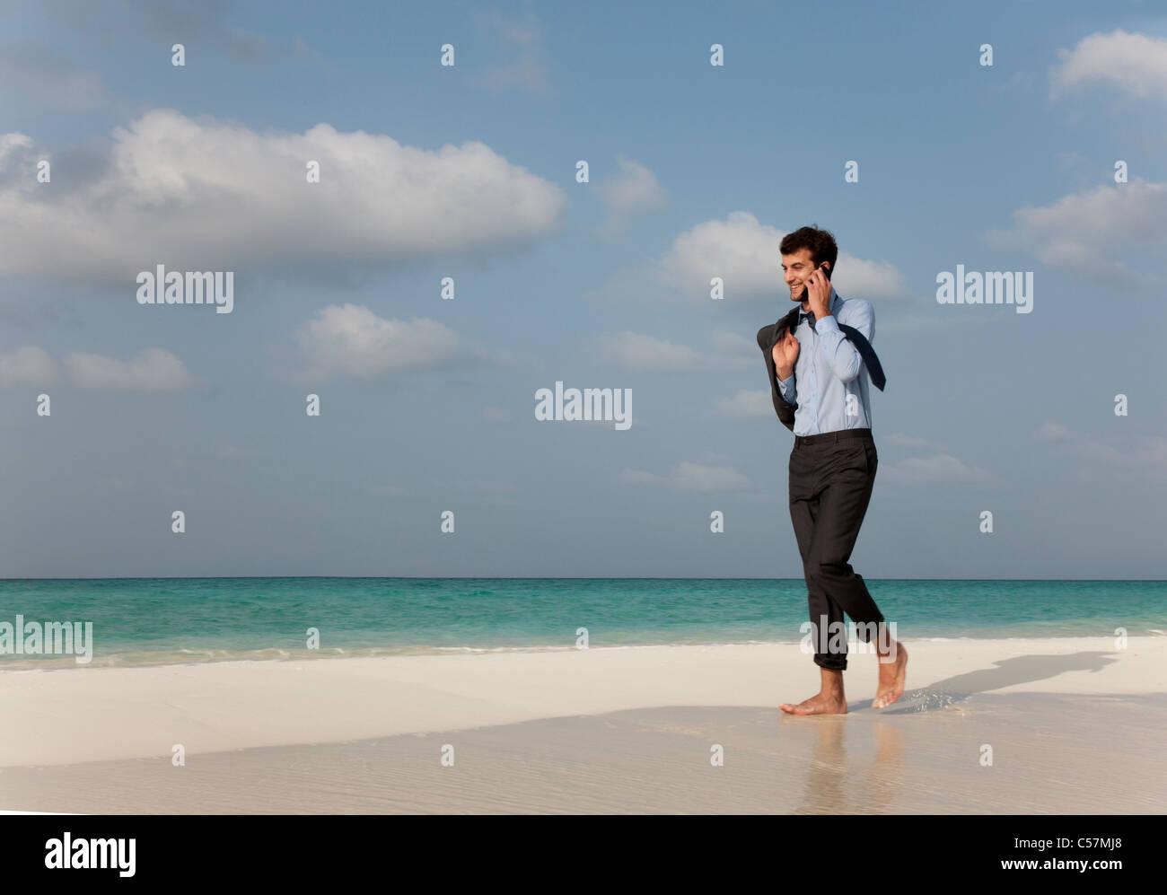 Businessman on cell phone on beach Stock Photo