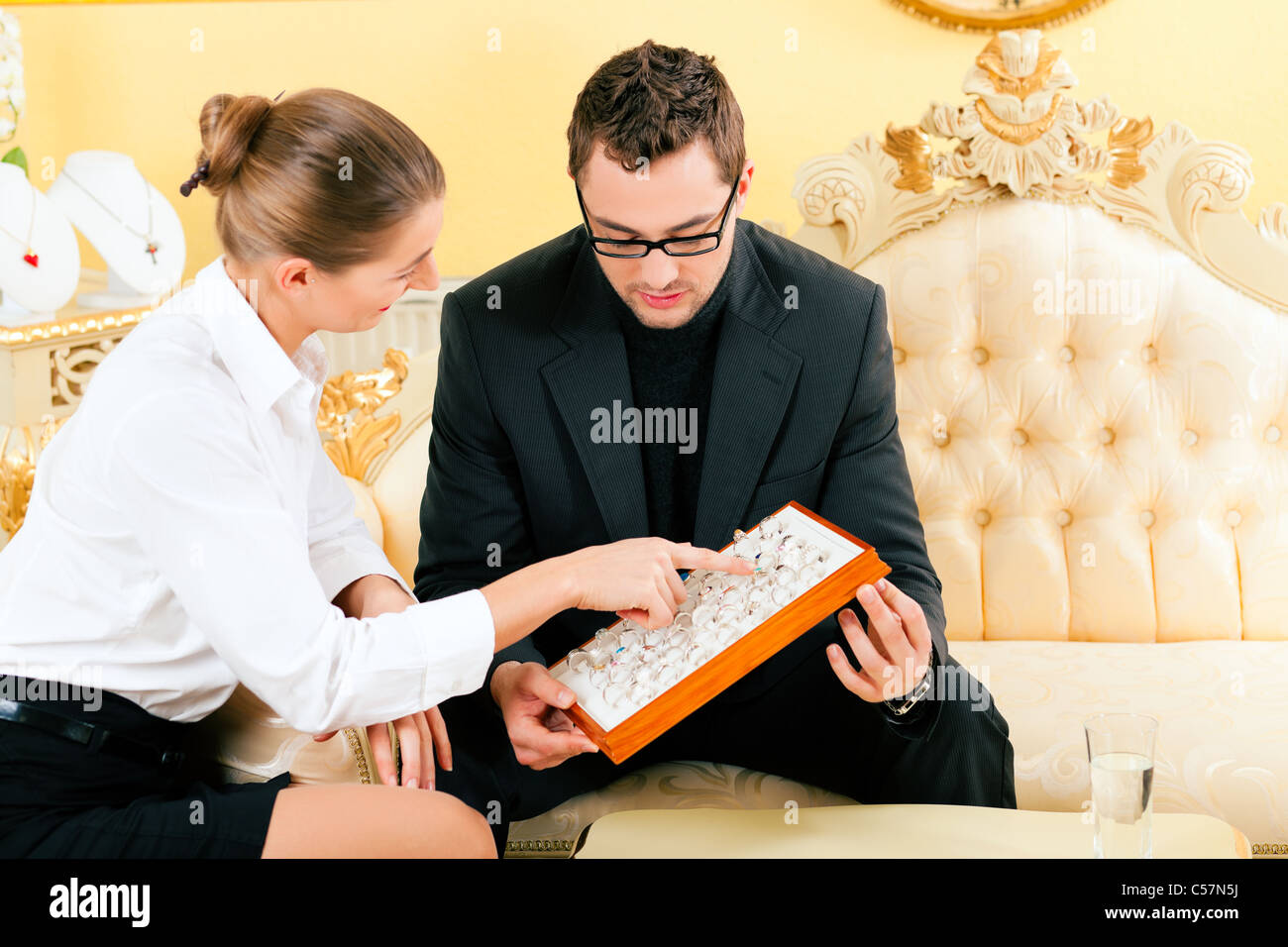 Man choosing a ring at the jeweller and gets consultancy by a shop assistant - Stock Image