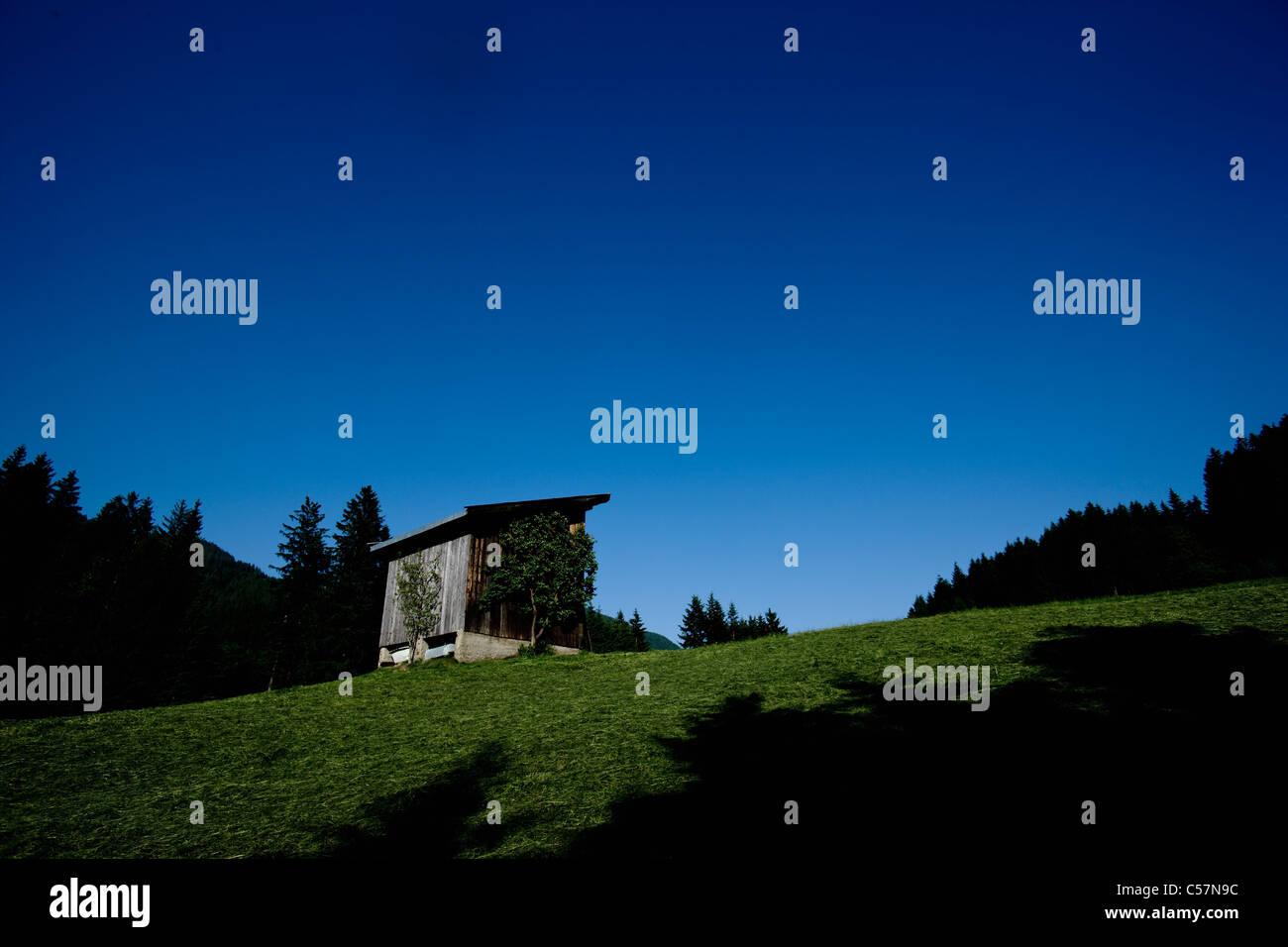 Shack on hillside against blue sky - Stock Image