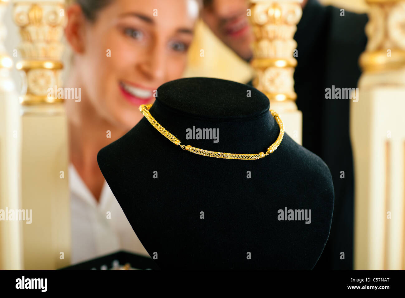 Woman at the jeweller is looking for jewellery - Stock Image