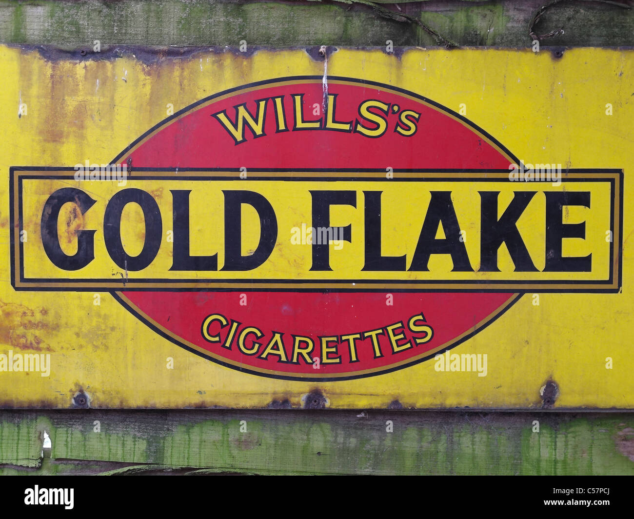 An old enamel sign advertising Wills's 'Gold Flake' cigarettes. - Stock Image
