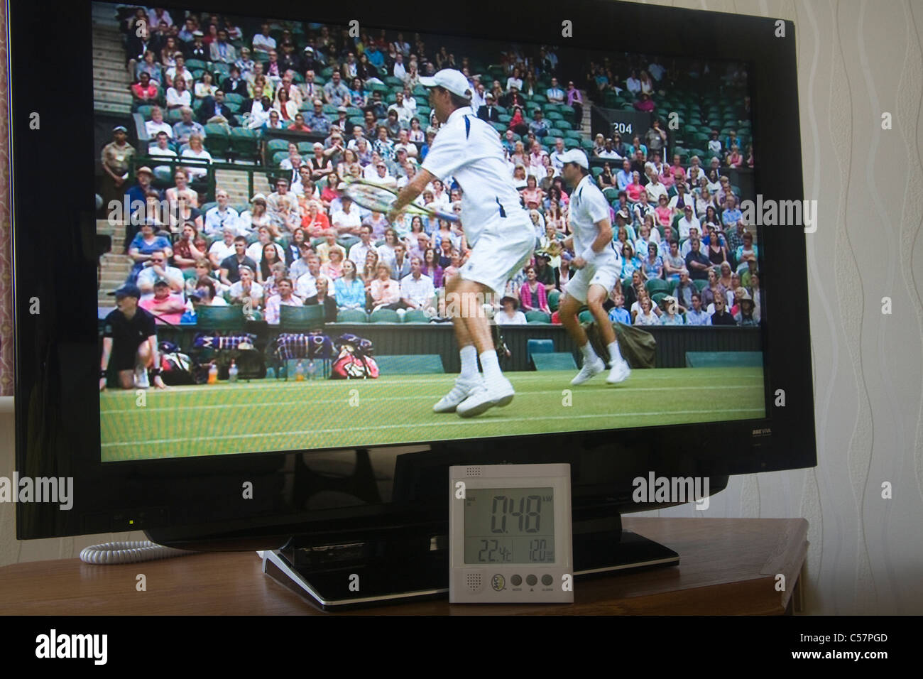 Owl electricity power usage monitor in front of a flat screen television set showing Wimbledon doubles tennis final - Stock Image