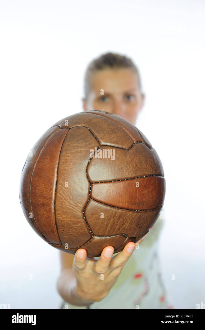 young woman holding an old fashion leather football. - Stock Image