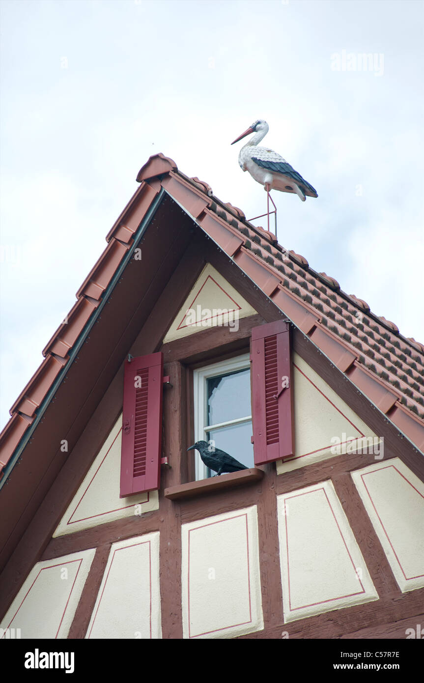 Detail of an old house with fachwerk or half-timbering with fake birds on it in the city of Haslach, Schwarzwald, - Stock Image