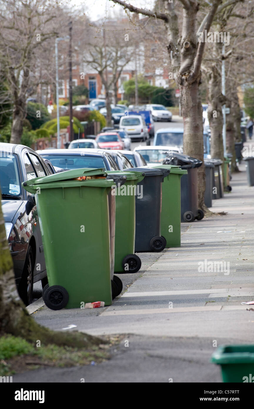 Wheelie bins containing household waste waiting for collection outside a house in England. Stock Photo