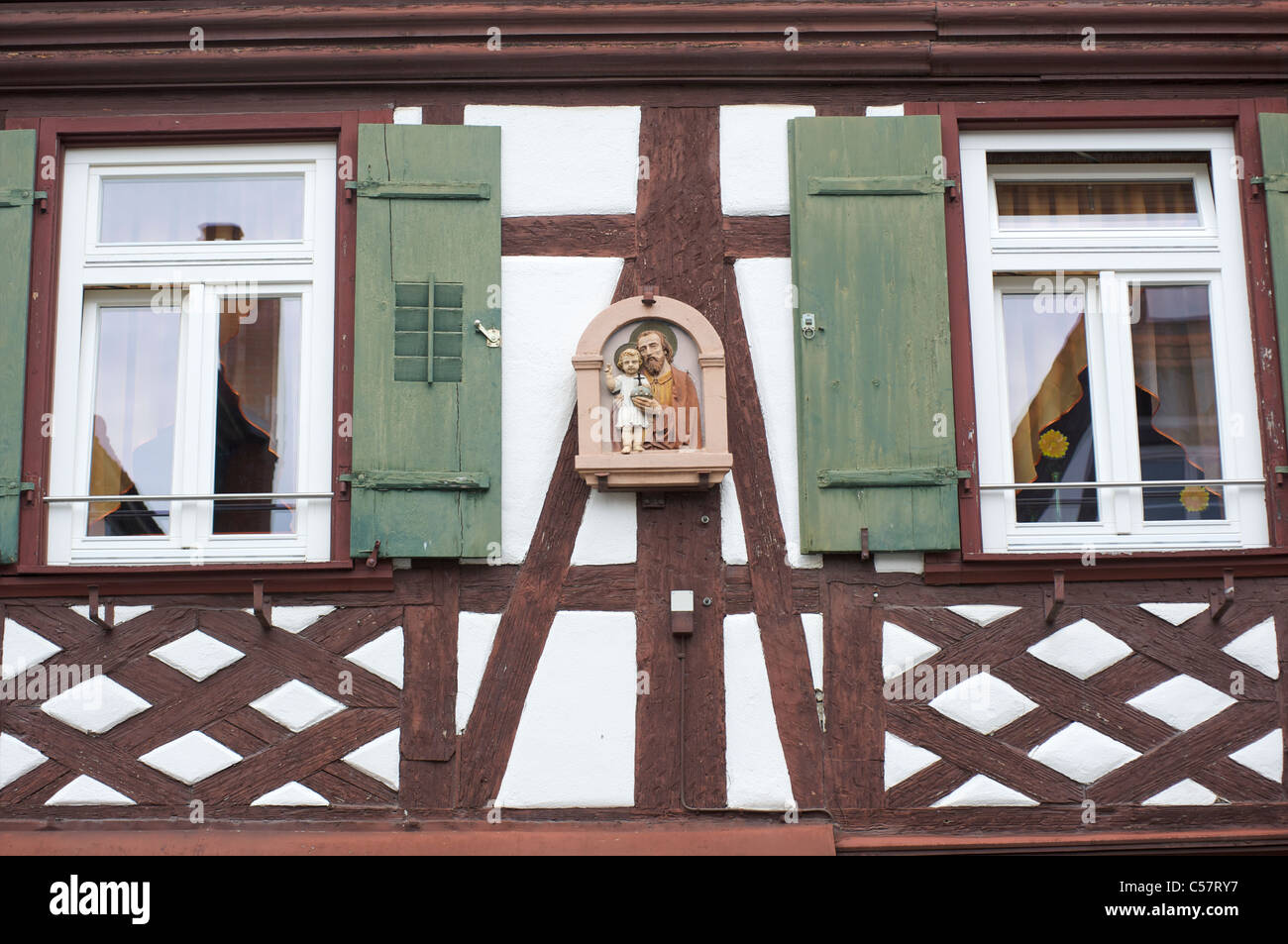 Detail of a house with fachwerk and a Christian mural in the city of Haslach, Schwarzwald, Baden-Wurttemberg, Germany - Stock Image