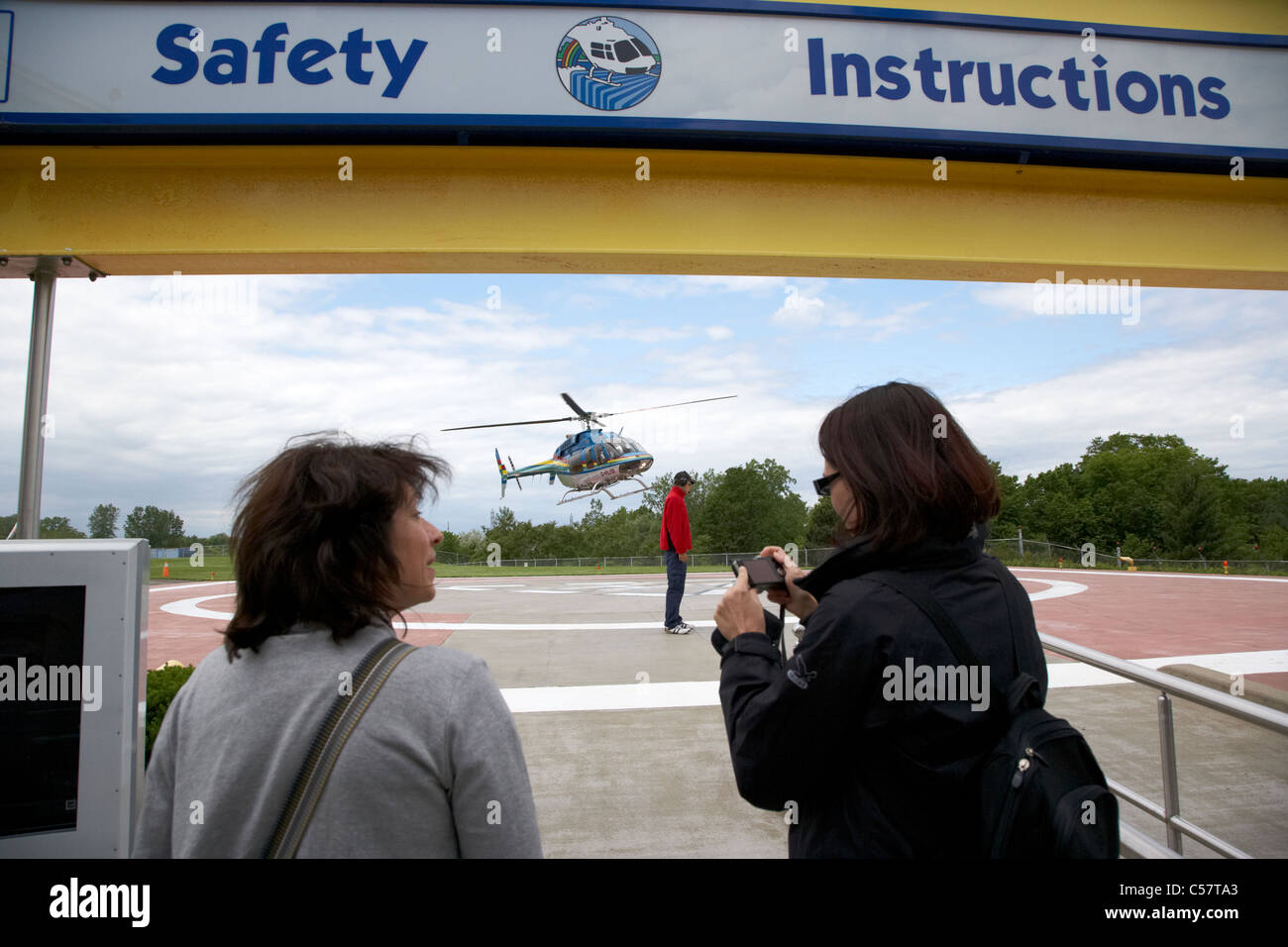tourists waiting as a helicopter lands for a flight over niagara falls ontario canada - Stock Image
