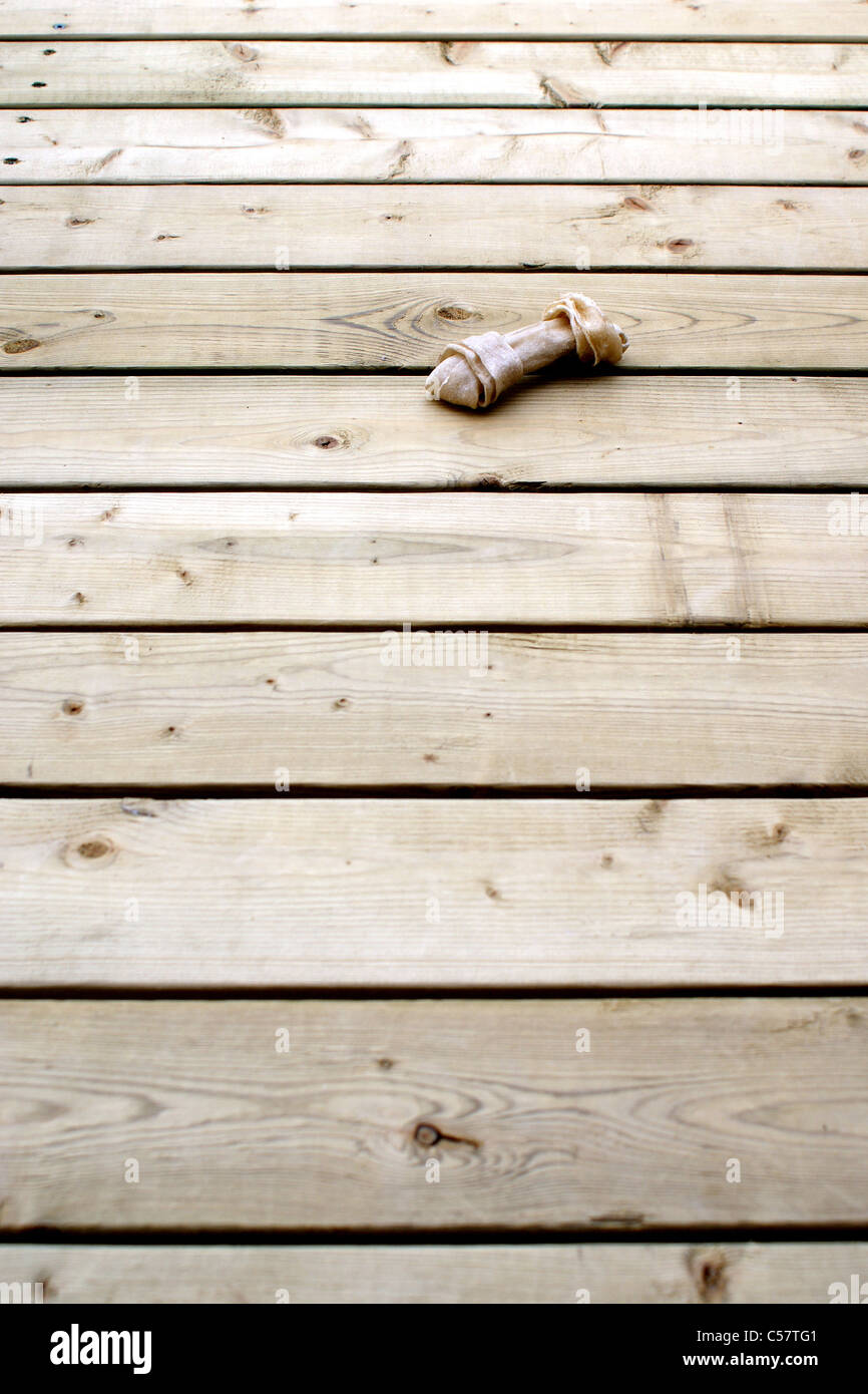 A dog's rawhide bone chew toy sits on wooden boards. - Stock Image