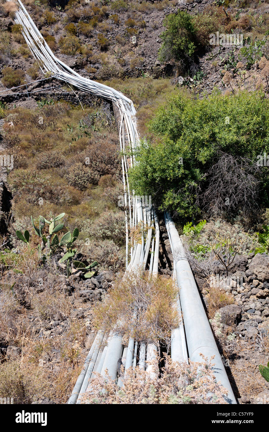 Water pipes carrying irrigation water supplies through a barranco in the Guia de Isora area of Tenerife Canary Islands - Stock Image