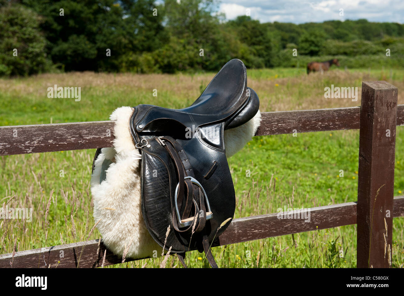 Saddle on post and rail fence ready to tack up horse UK equestrian - Stock Image