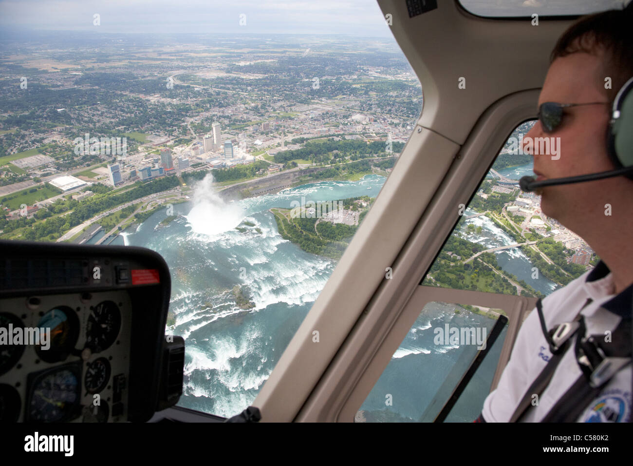 pilot flying helicopter flight over niagara falls ontario canada focus on falls - Stock Image