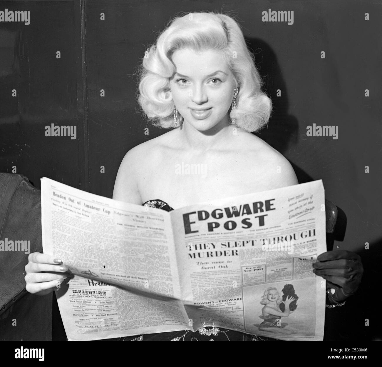 British actress Diana Dors reading the Edgware Post newspaper 1954 - Stock Image
