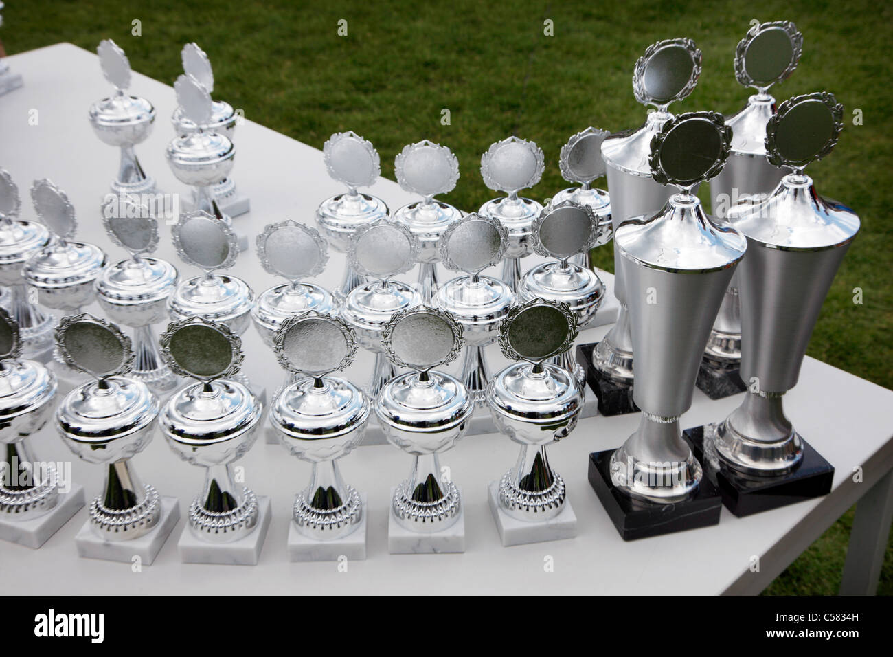 Silver cups waiting for winners of a sports competition. - Stock Image
