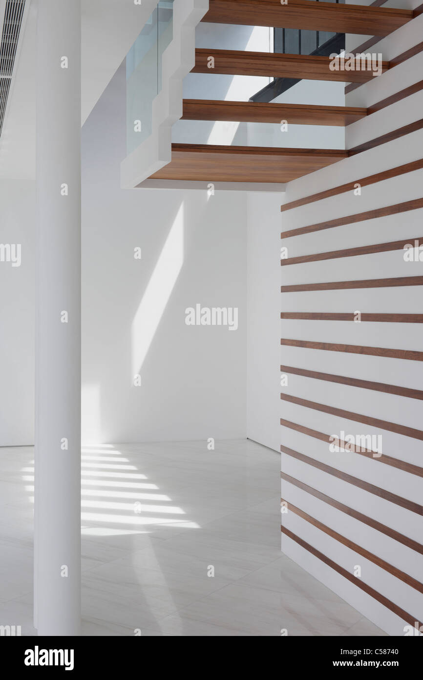 Modern white living space, view from under steps. - Stock Image