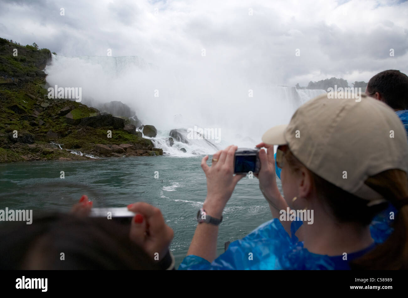 tourists in blue plastic waterproof ponchos taking photos at the american falls on maid of the mist niagara falls - Stock Image