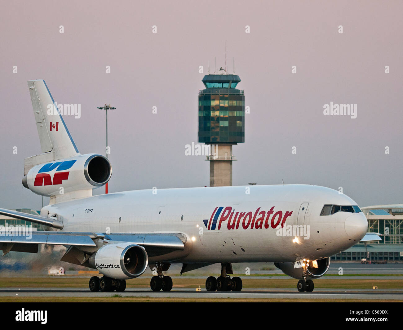An air cargo DC10-30F jet in Purolator Courier livery is seen as it lands at Vancouver International Airport. - Stock Image