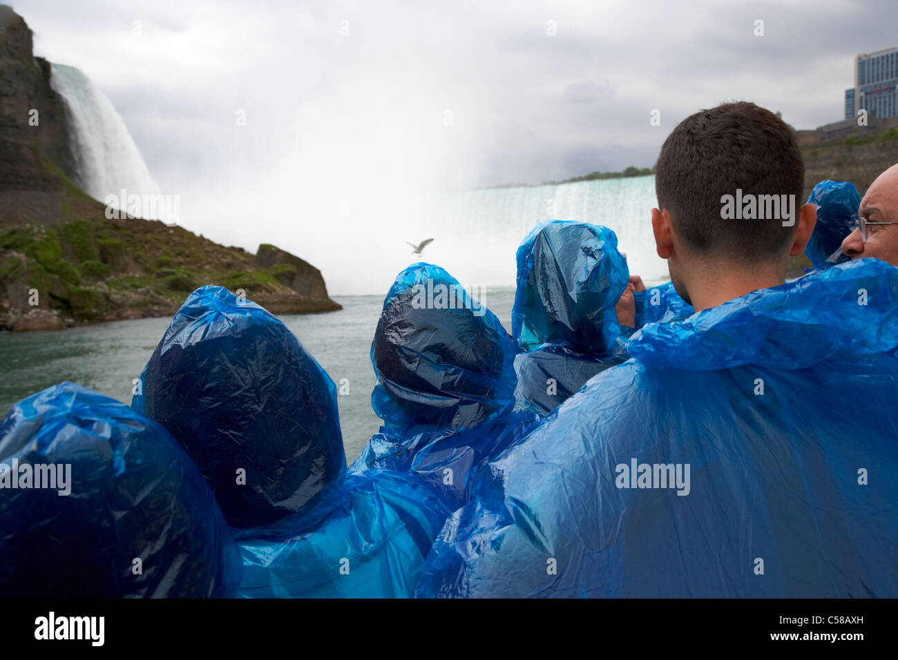 tourists in blue plastic waterproof ponchos approaching the horseshoe falls on maid of the mist niagara falls ontario - Stock Image