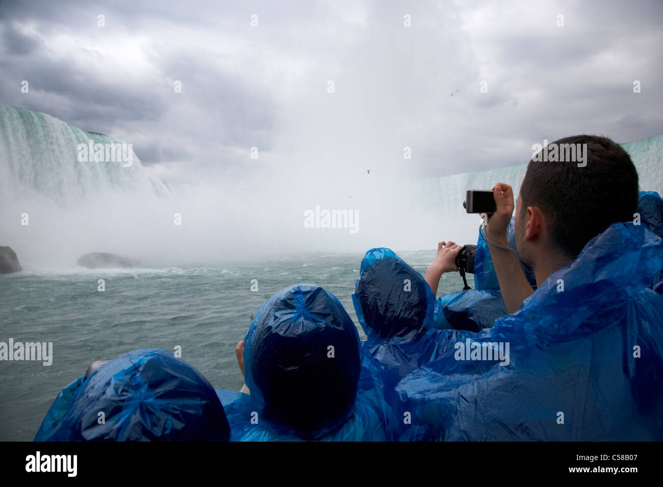 tourists wearing blue plastic waterproof ponchos take photos on the maid of the mist niagara falls ontario canada - Stock Image