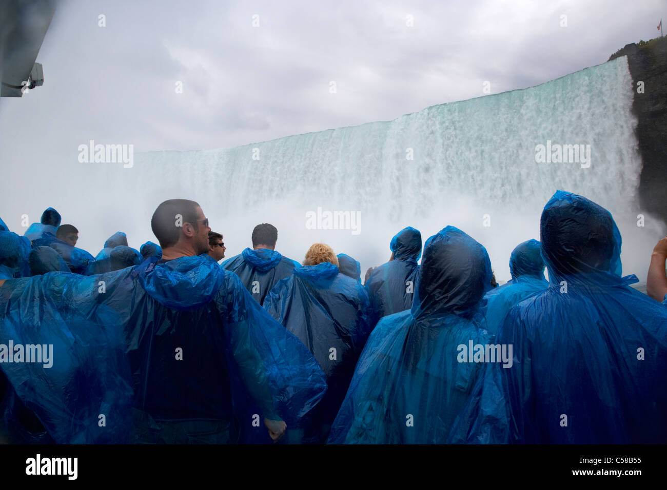 tourists getting wet in blue plastic waterproof ponchos at the maid of the mist niagara falls ontario canada - Stock Image
