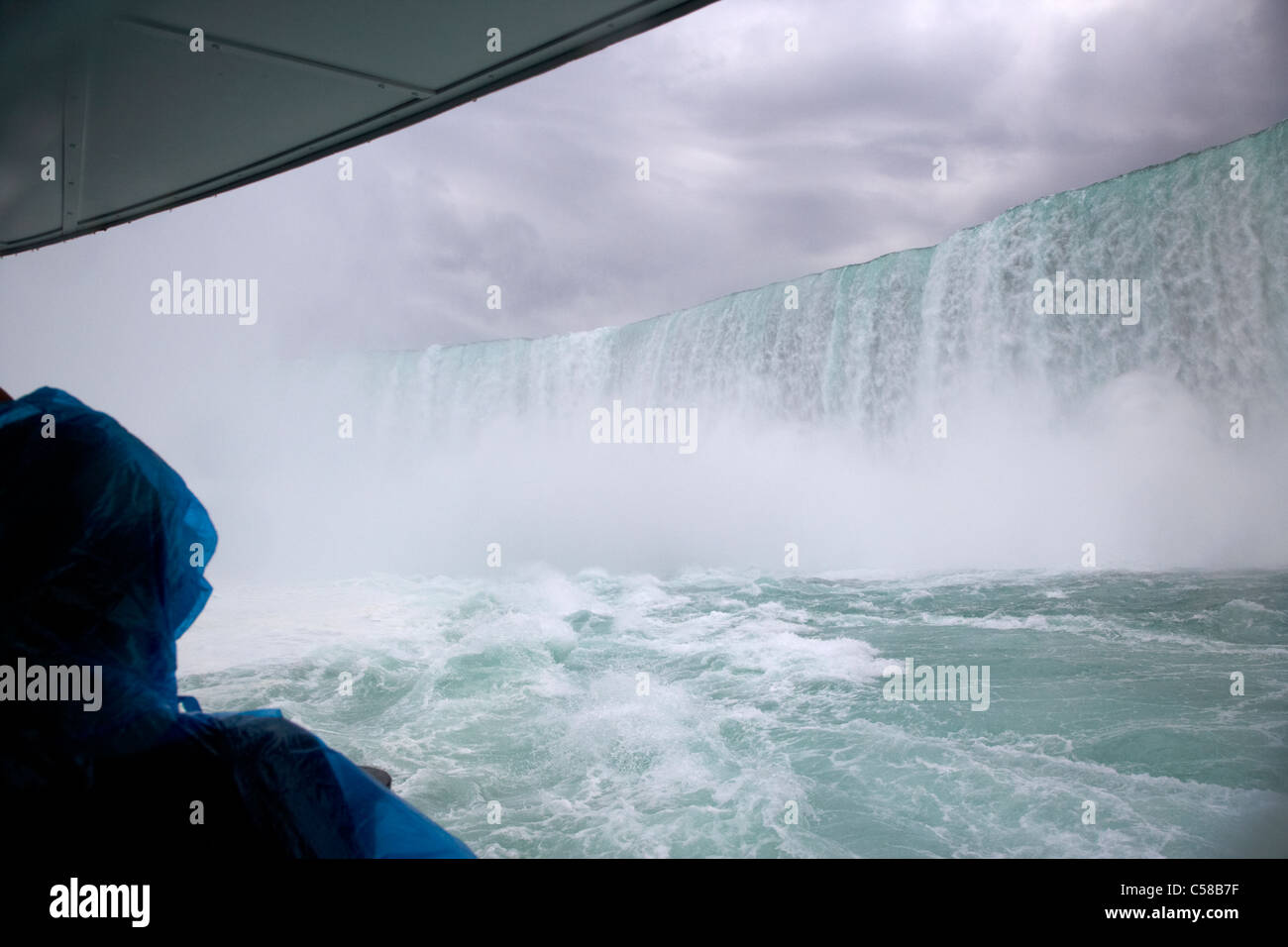 tourist in blue plastic waterproof poncho under the horsehoe falls on the maid of the mist niagara falls ontario - Stock Image