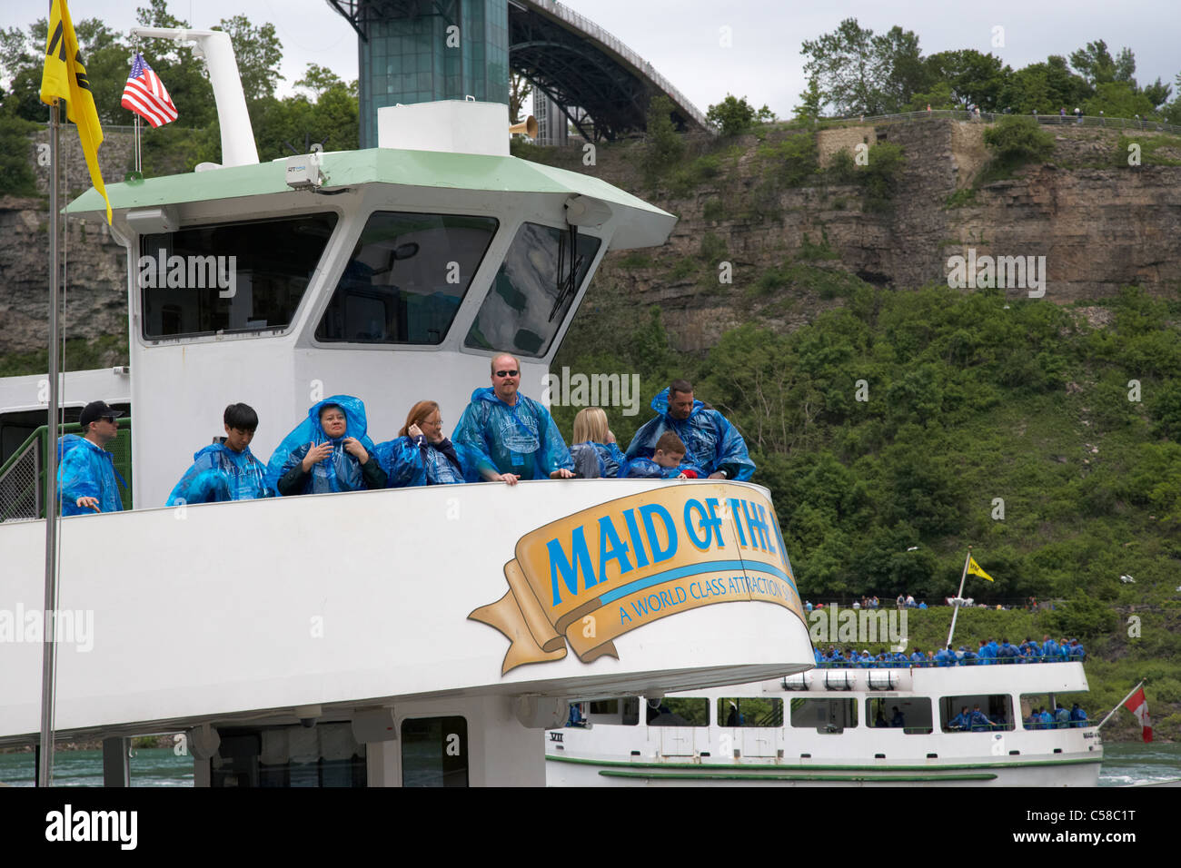 tourists in blue plastic waterproof ponchos boarding the upper deck of the maid of the mist niagara falls ontario - Stock Image