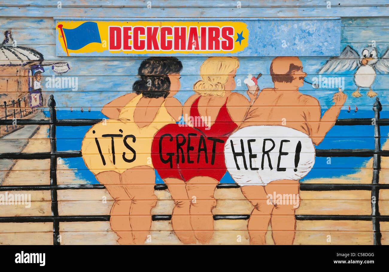 saucy seaside postcard style people painted on deckchair beach hut - Stock Image