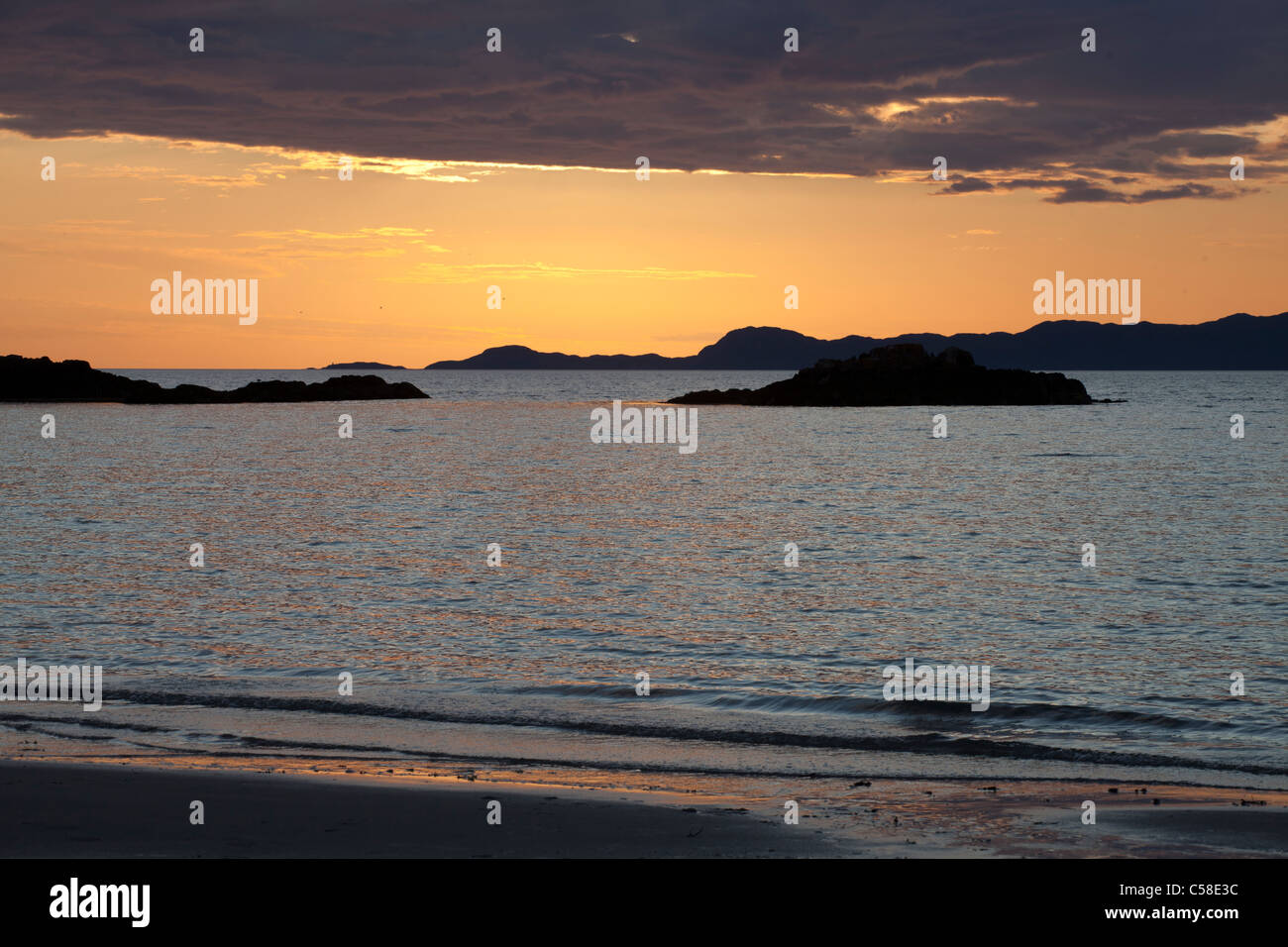 Sunset over the Scottish Isles as seen from Camusdarach in the Western Highlands, - Stock Image