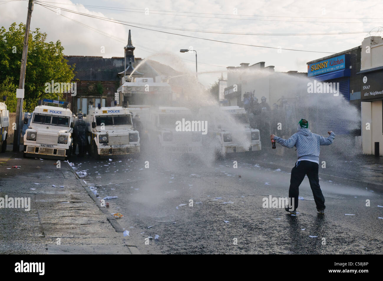 Rioter confronts police water cannon - Stock Image