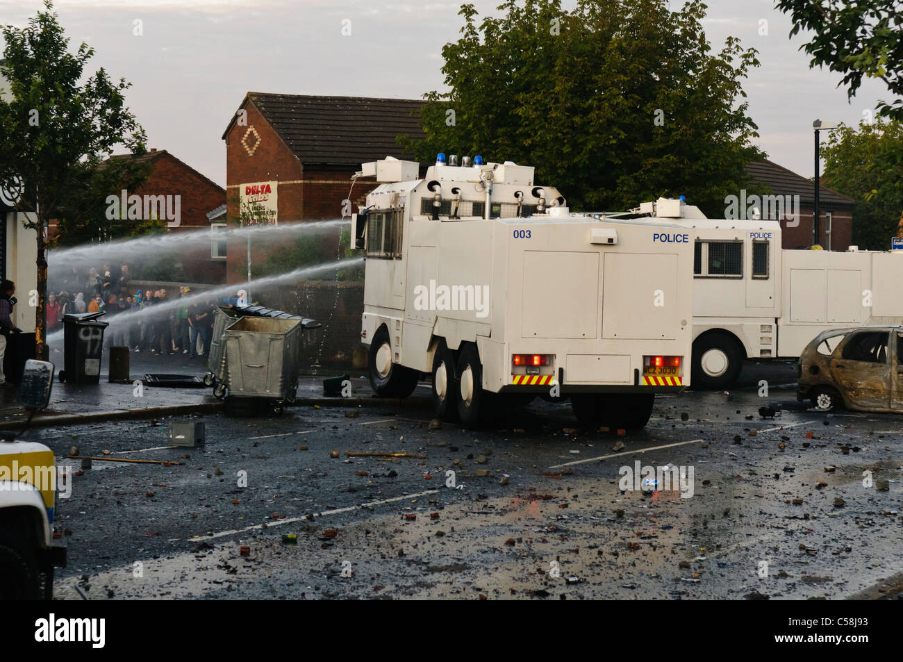 Police water cannon disperse rioters - Stock Image