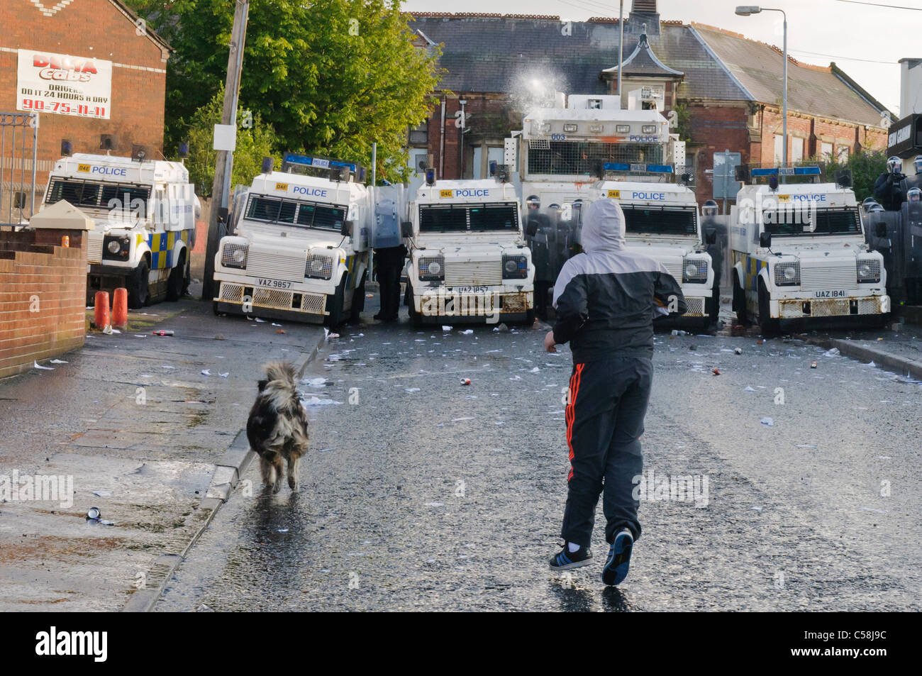 Rioter confronts police as water cannon is fired at him - Stock Image
